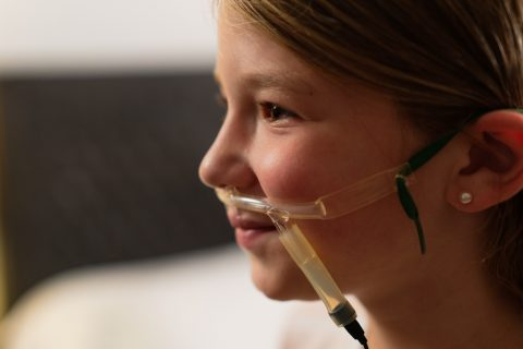 A child wearing a nasal cannula and airflow sensor as part of a Snap Diagnostics' home sleep apnea test