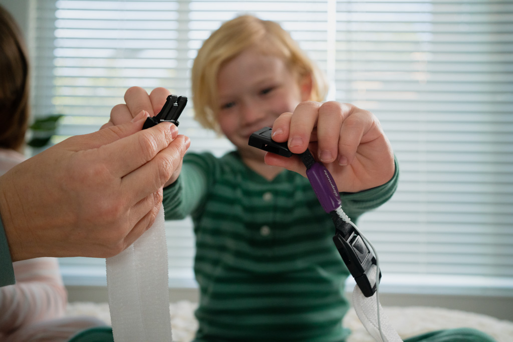 A parent helps her child apply the respiratory effort sensor and chest belt