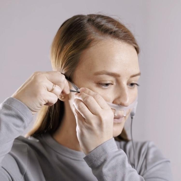 An adult wearing a nasal cannula and airflow sensor as part of a Snap Diagnostics' home sleep apnea test